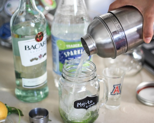 pouring the light mojito into a mason jar