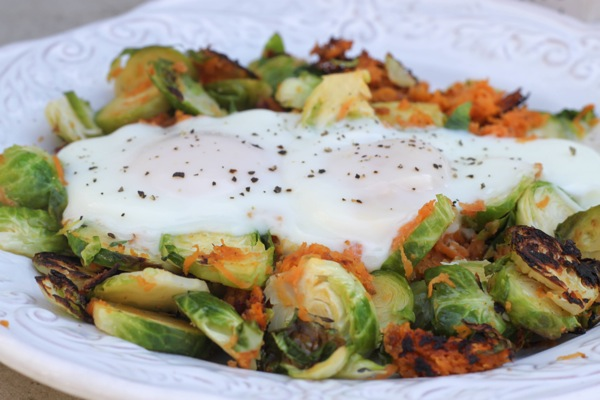 Eggs in a basket of brussels sprouts and sweet potato. Whole 30 and paleo friendly!