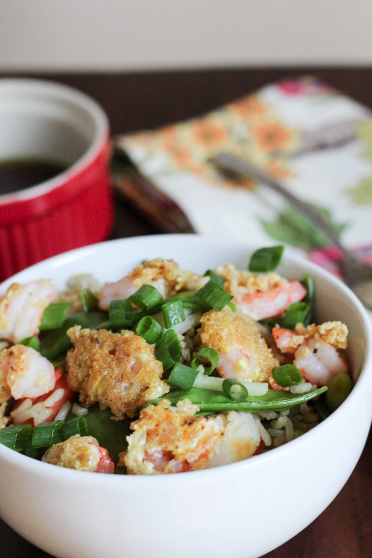 This crispy shrimp and rice bowl is a healthier way to satisfy your fried food craving! Loaded with veggies and drizzled with a soy-ginger glaze, this is the healthy dinner that you'll crave! fitnessista.com #shrimprecipes #crispyshrimp #healthydinner