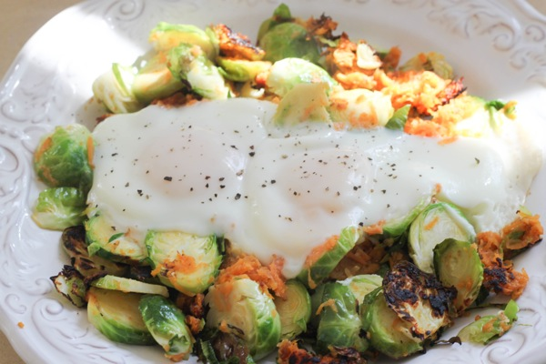 Eggs in a basket basket with sweet potatoes and brussels sprouts