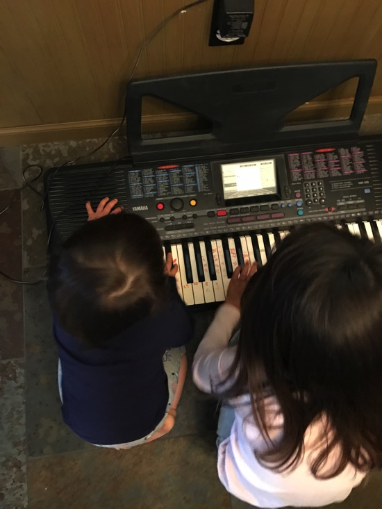 The girls playing the keyboard