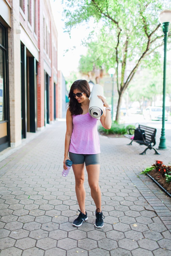 water bottle and yoga mat in hand