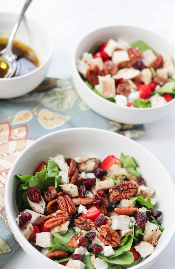 This grilled chicken salad with pecans and strawberries is the perfect bridge between summer and fall flavors. Bright end-of-summer strawberries mix with warm maple-roasted pecans in this appealing, sweet and savory combination. fitnessista.com