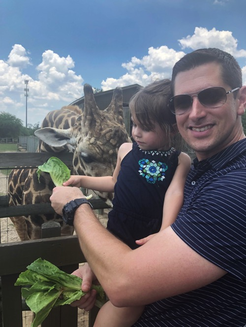Tom and P feeding giraffes