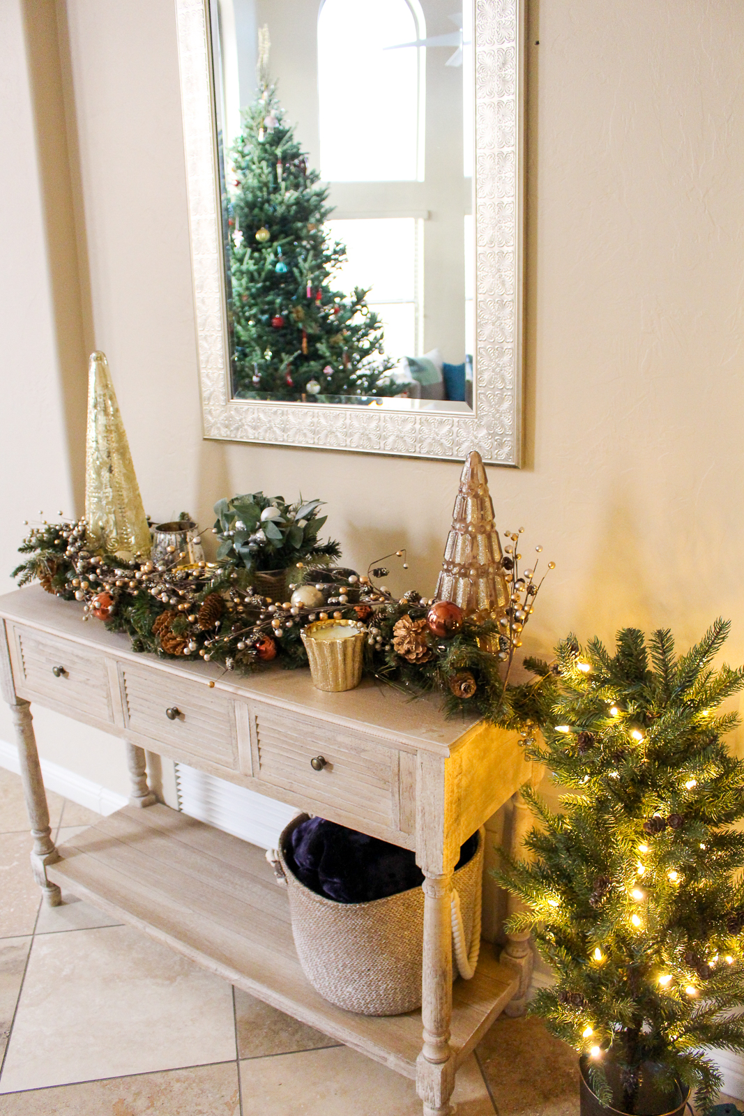 End table with bronze and gold holiday decorations, gold Christmas trees and candles