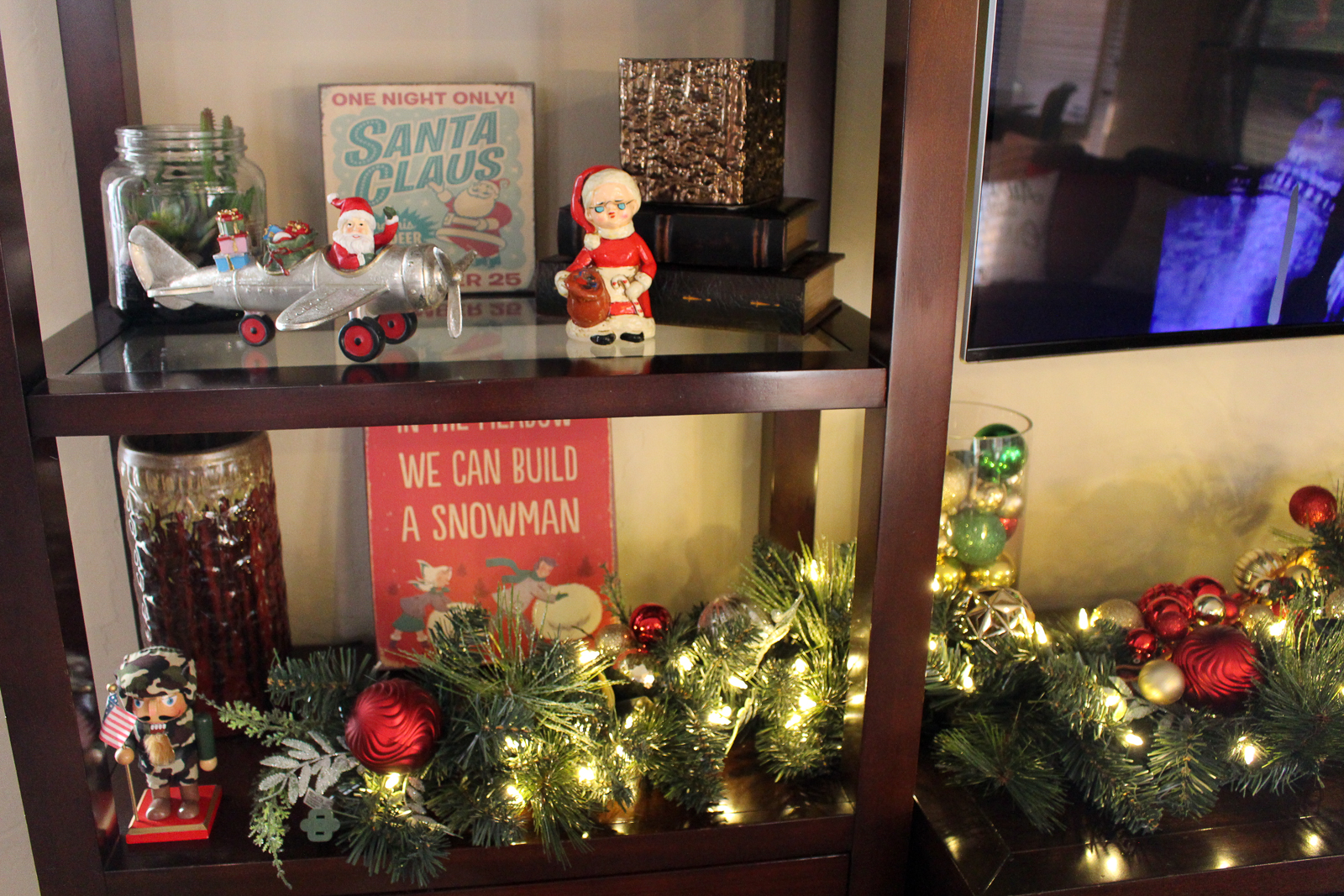Holiday decorations on an entertainment center, including vintage Santa figurines and an illuminated garland